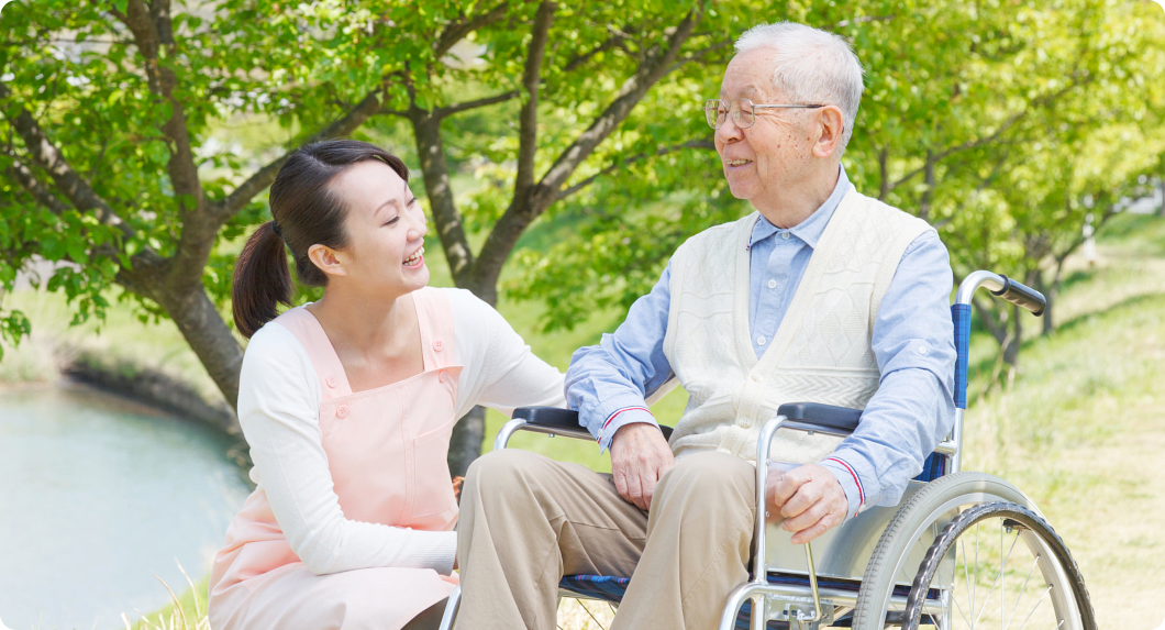 old man on wheelchair and his caregiver smiling